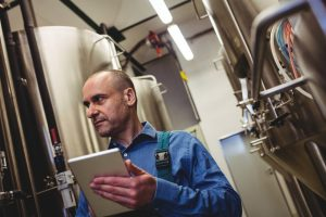 Low angle view of manufacturer with digital tablet examining machinery at brewery